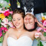 Hochzeitspaar liegt auf einer bunten Blumenwiese