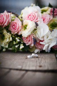 Trauringe vor zartem Brautstrauß auf Holztisch