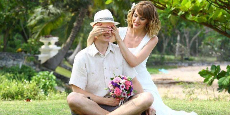 Braut überrascht den Bräutigam auf einer Wiese in den Flitterwochen